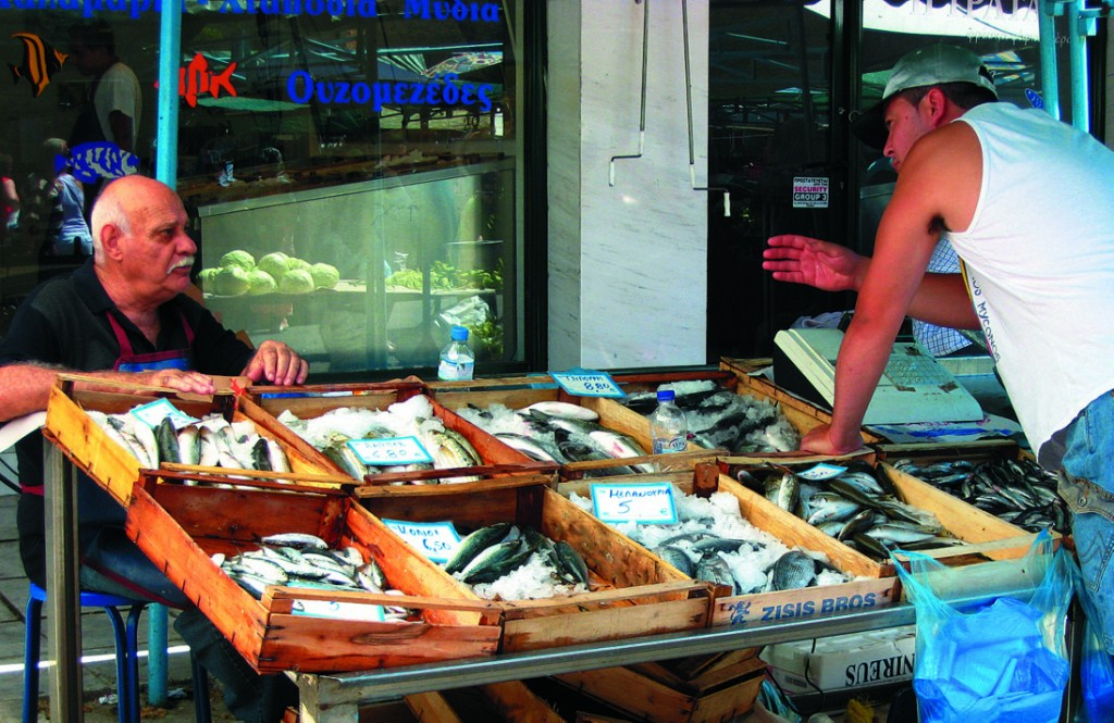 Greek men haggling over fish at the market